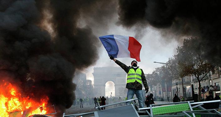 Um manifestante segura a bandeira da França sobre uma barricada em chamas na Avendia Champs-Elysees, com o arco do Triunfo ao fundo, durante a manifestação contra o aumento de combustíveis no país. Foto de 24 de novembro de 2018.