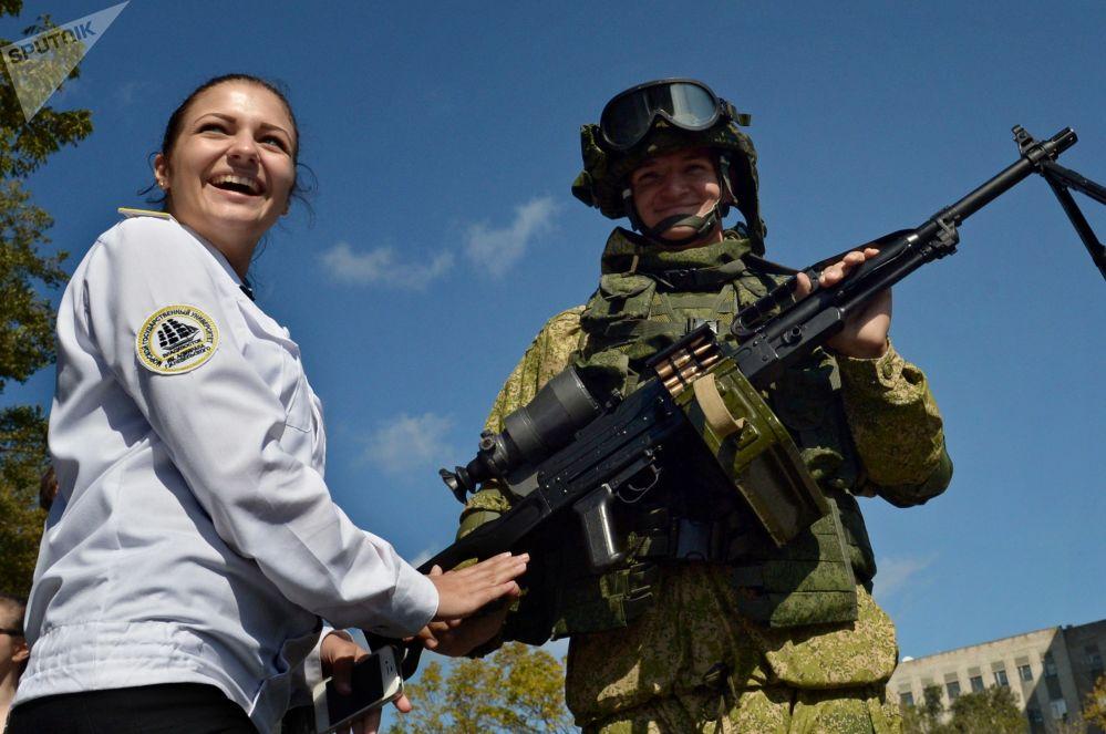 Visitante posando ao lado de um fuzileiro naval em uma exposição de armamentos