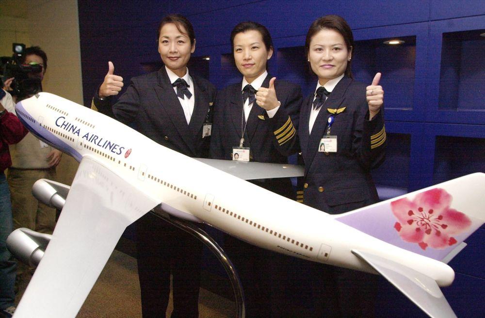 Pilotas da companhia aérea China Airlines, perto de um modelo da Boeing 747-400, em Taipé (Taiwan), 4 de novembro de 2002