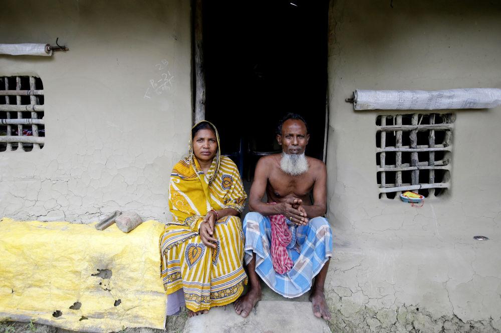 Um casal da ilha de Ghoramara posa perante sua nova casa de barro após a anterior ter sido levada durante a maré alta na ilha.