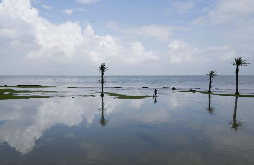 Menino pescando durante maré baixa na ilha de Ghoramara.