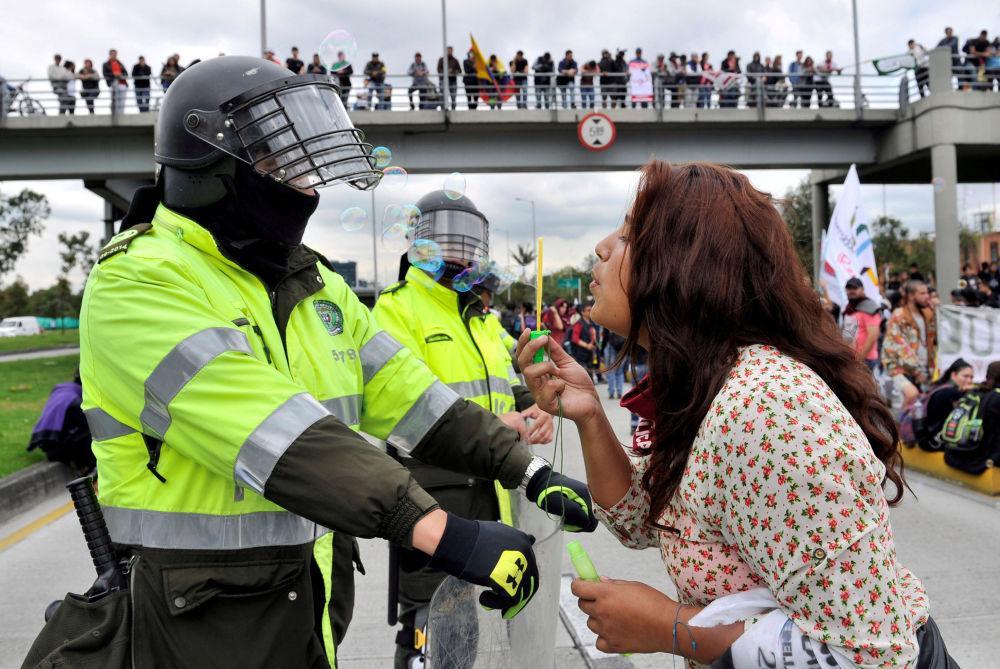 Estudante perto da polícia durante um protesto em Bogotá, Colômbia, 29 de novembro de 2018