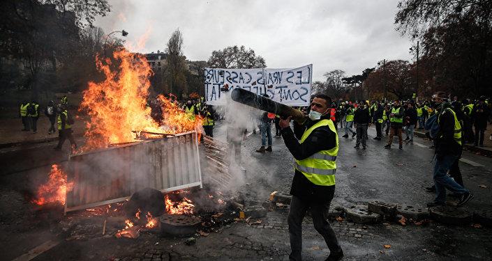 Manifestantes construindo barreira durante um protesto de coletes amarelos contra aumento de preços de combustíveis, Paris, 1º de dezembro de 2018