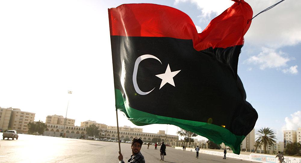 Líbio agita bandeira nacional enquanto manifestantes se reúnem para protesto contra a munição do Exército líbio, na cidade de Benghazi, em 27 de fevereiro de 2015