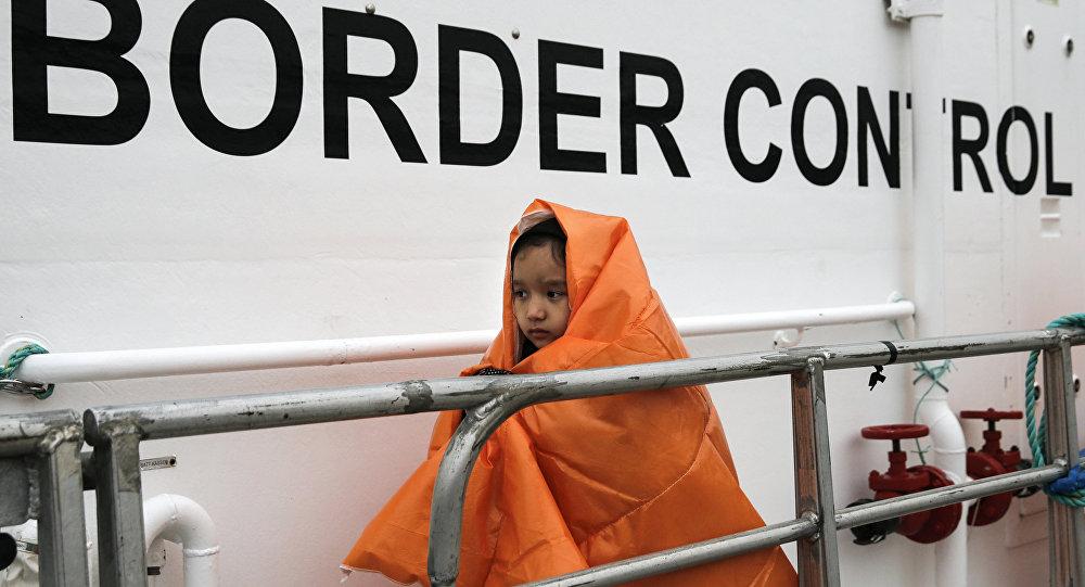 Uma menina refugiada, coberta com um cobertor e resgatada em alto mar, prepara-se para desembarcar um navio-patrulha da Frontex no porto de Mitilene, na ilha de Lesbos, na Grécia (arquivo)