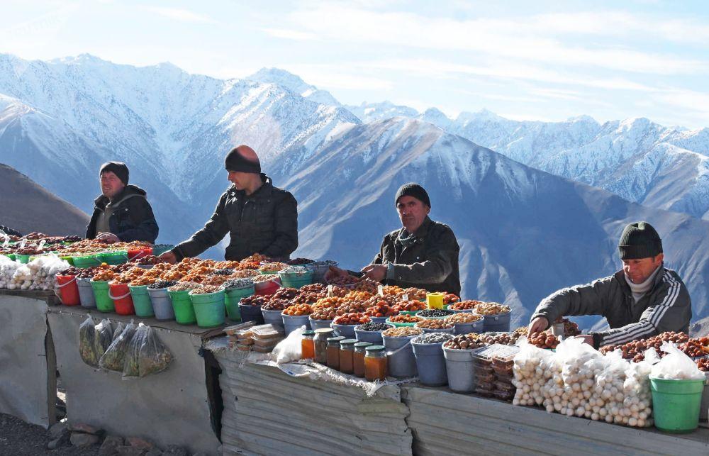 Vendedores de frutas secas em uma passagem nas montanhas no Tajiquistão