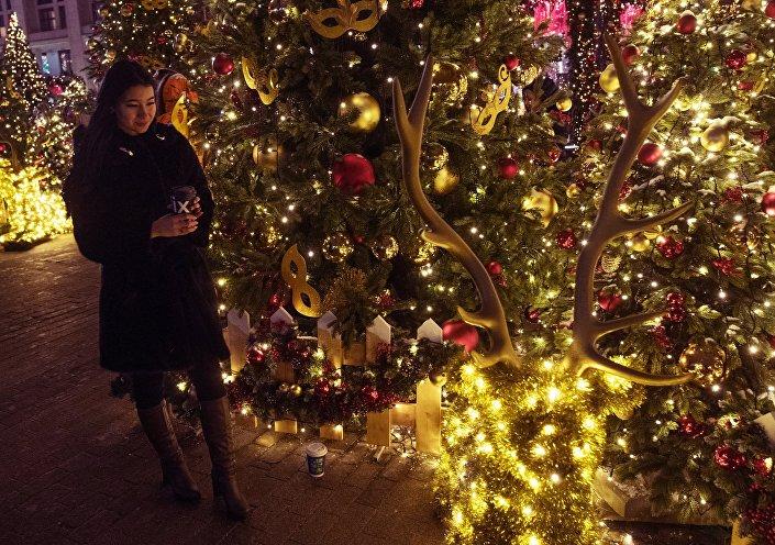 Turista em meio a decorações natalinas na praça Manezhnaya