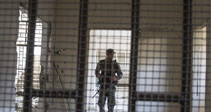 Um membro das Forças Democráticas da Síria (SDF) apoiadas pelos EUA caminha dentro de uma prisão construída por combatentes do Estado Islâmico.