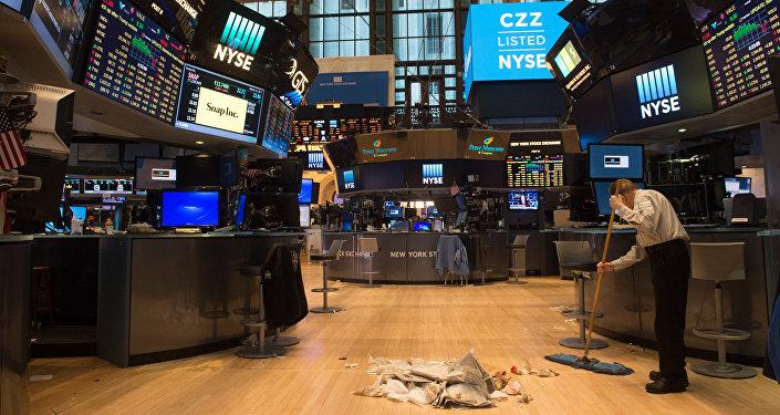 Um trabalhador varre o chão depois do fechamento do Dow Jones na Bolsa de Nova York.