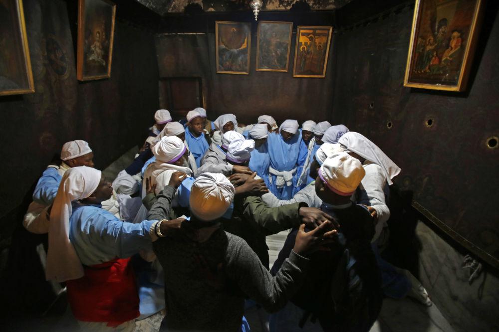 Peregrinos nigerianos rezam dentro da Gruta, que se acredita ser o local exato onde Jesus Cristo nasceu, na Basílica da Natividade, na cidade bíblica da Cisjordânia, em Belém, 24 de dezembro de 2018