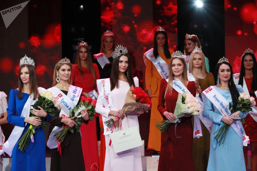 Participantes russas, segurando flores, posam para foto durante competição de beleza Miss Moscow 2018 (Rússia), 24 de dezembro de 2018