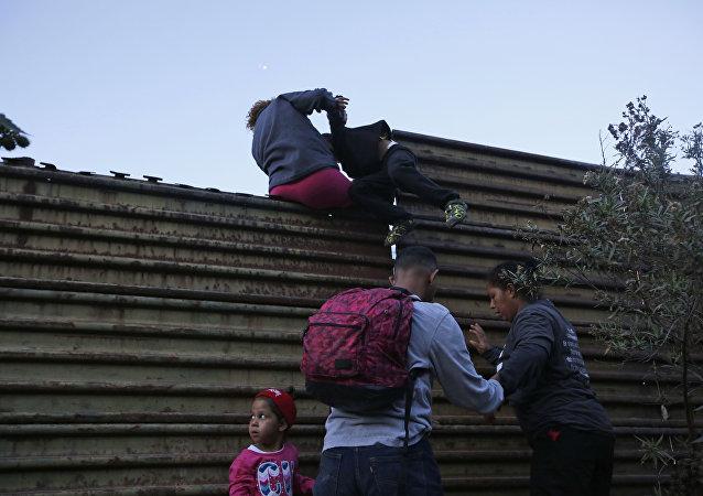 Migrantes hondurenhos ajudam-se mutuamente a atravessar fronteira dos EUA até San Diego, Califórnia.