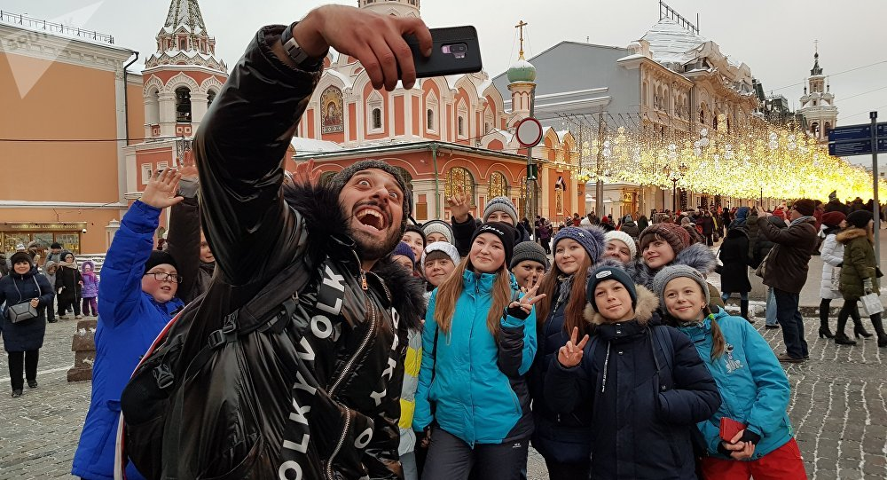 Crianças, durante excursão pela Praça Vermelha, pedem para tirar foto com Tomer Savoia, que virou meme mais comentado na Rússia durante a Copa, 27 de dezembro de 2018