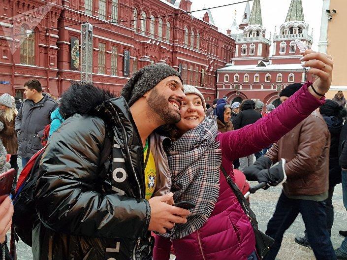 Jovem russa tira selfie com Tomer Savoia na Praça Vermelha, 27 de dezembro de 2018