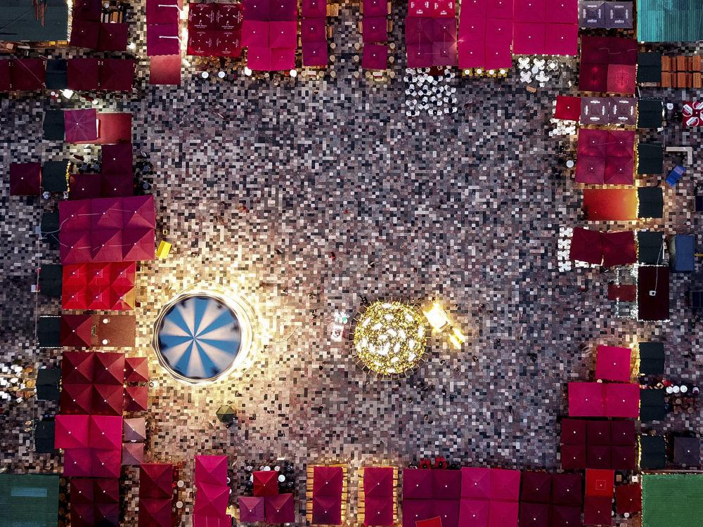 Imagem mostra vista aérea da praça principal da cidade de Tirana, na Albânia, iluminada com decorações natalinas e rodeada por um mercado aberto de Natal, em 24 de dezembro de 2018