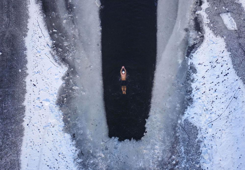 Imagem tirada de cima de um homem nadando em um lago congelado, com temperaturas abaixo de -20 graus Celsius, em Shenyang, na província de Liaoning, nordeste da China