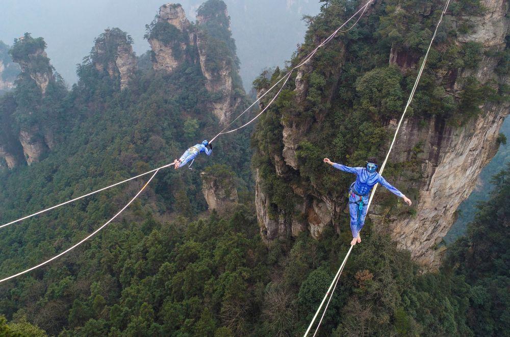 Dois participantes, vestidos como personagens do filme Avatar, durante a competição de Slackline nas montanhas Yuantszyatsze no centro da Província de Hunan, na China