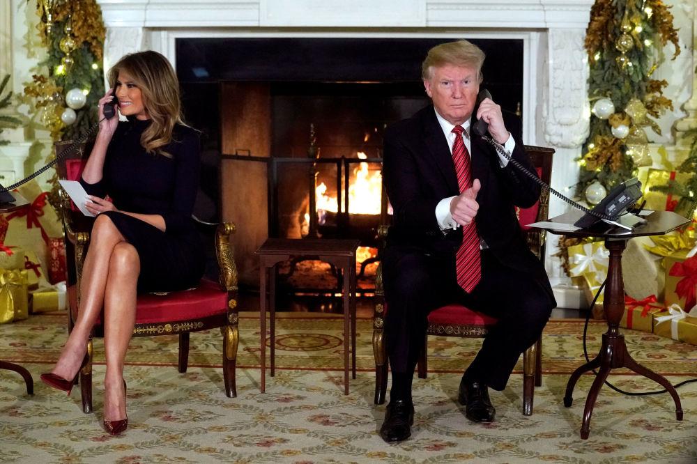Presidente dos EUA, Donald Trump, e a primeira-dama, Melania Trump, falando por telefone com crianças sobre a passagem do Papai Noel na véspera de Natal