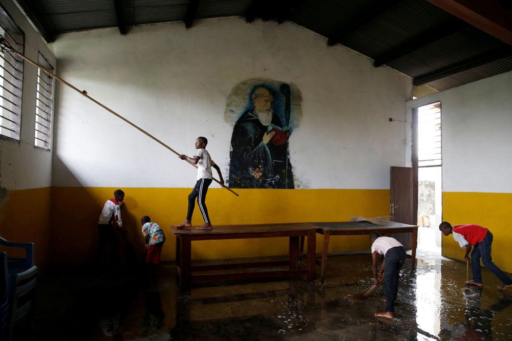 Garotos ajudam a limpar igreja de Saint-Benoît na preparação para o Natal, em Kinshasa
