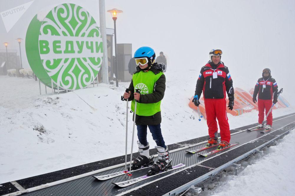 Atletas sobem para o topo da pista depois de esquiarem na estação Veduchi, na república de Chechênia