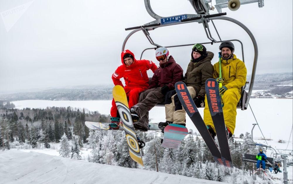 Turistas satisfeitos no teleférico durante a abertura da temporada de esqui e snowboard no território do centro de recreação ativa Yalgora, em Karelia
