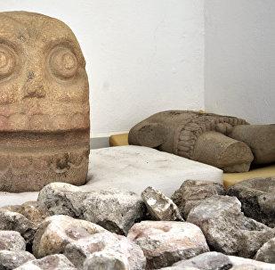 Duas esculturas de pedra parecidas com caveiras e uma de tronco representando o deus Xipe Totec encontradas durante as escavações no estado de Puebla, México