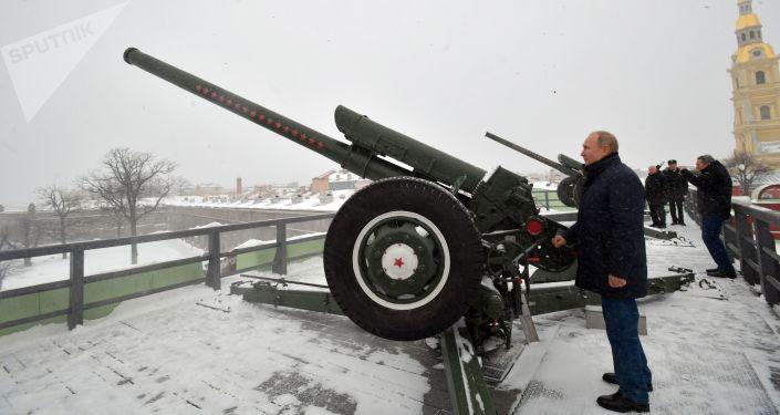 Vladimir Putin efetuando o tradicional disparo de canhão durante uma visita à Fortaleza de São Pedro e São Paulo na cidade de São Petersburgo