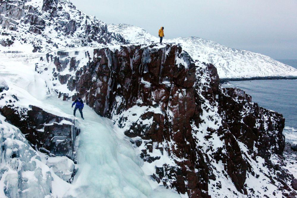 Turista no topo de uma cachoeira congelada da península de Kola (extremo norte da Rússia)
