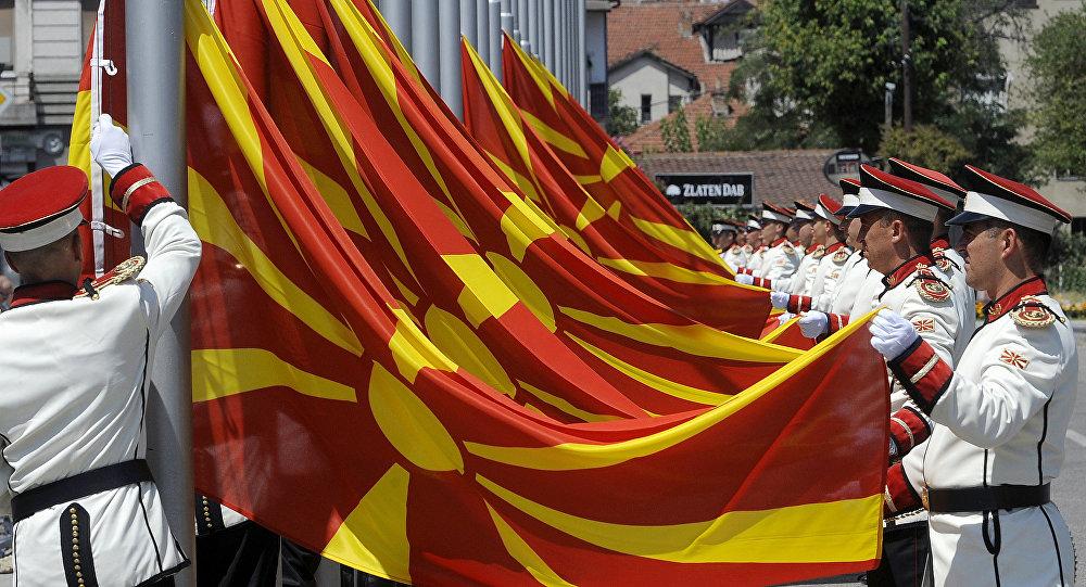 Oficiais de guarda do exército macedônio mudam as bandeiras nacionais durante uma cerimônia especial em frente ao prédio do governo na capital da Macedônia, Escópia.