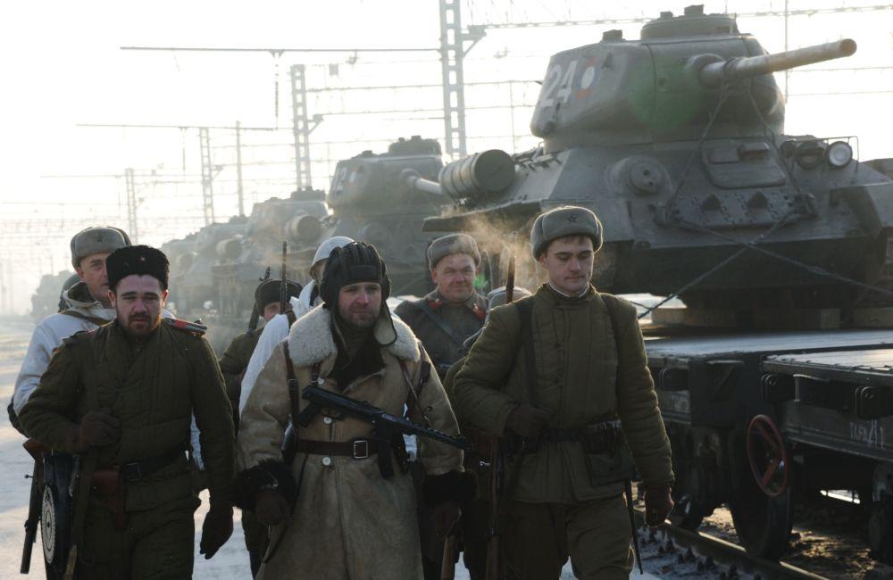 Militares russos andando ao lado do trem que está transportando tanques T-34