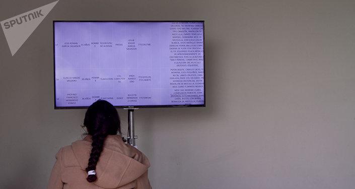 Mulher busca na lista de feridos parente desaparecido depois da explosão de oleoduto da Pemex
