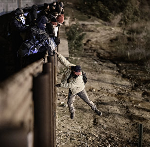 Um migrante em Tijuana, México pula a fronteira para entrar na cidade americana de San Diego, na Califórnia (arquivo)