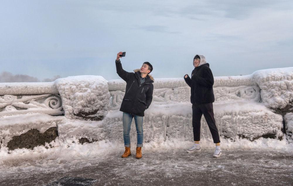 Pessoas tiram selfie com as cataratas do Niágara ao fundo, em Ontário, Canadá