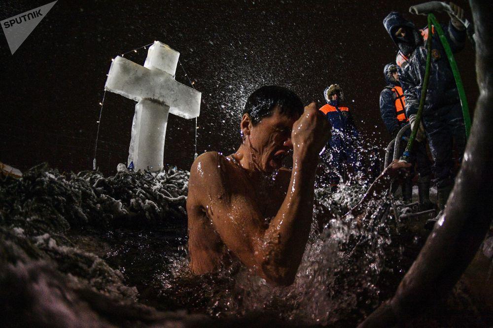 Homem durante o banho tradicional da festa da Epifania na Rússia