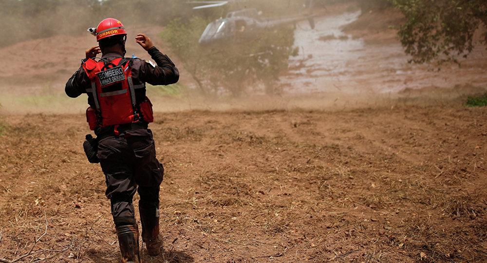 Um bombeiro gesticula perto de um helicóptero de resgate após uma barragem de rejeitos da mineradora brasileira Vale SA explodir em Brumadinho.