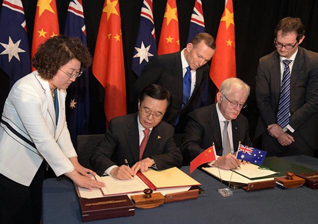 Premiê australiano, Tony Abbott, observa o ministro do Comércio chinês, Gao Hucheng, durante assinatura do tratado de livre-comércio