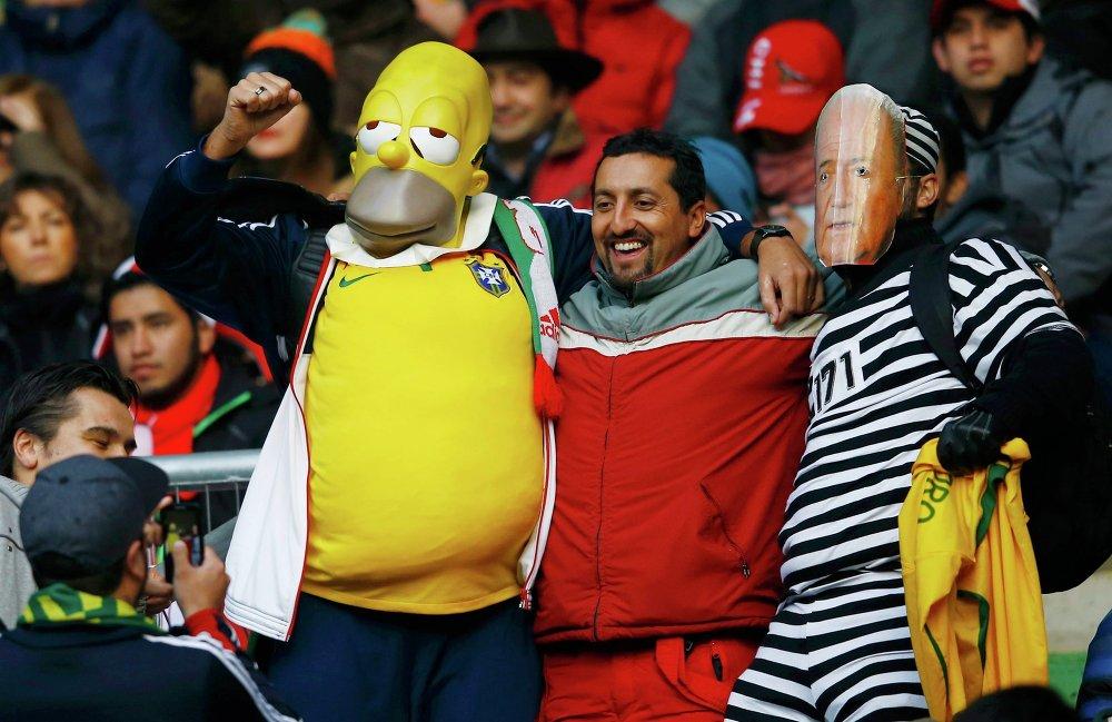 Torcedores brasileiros vestem máscara de Homer Simpson e do presidente da FIFA Joseph Blatter durante o jogo com o Peru em 14 de junho