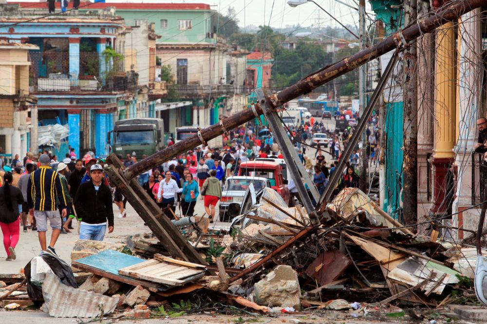 Cubanos caminham pelas ruas de Havana observando destroços de prédios depois do tornado na capital de Cuba