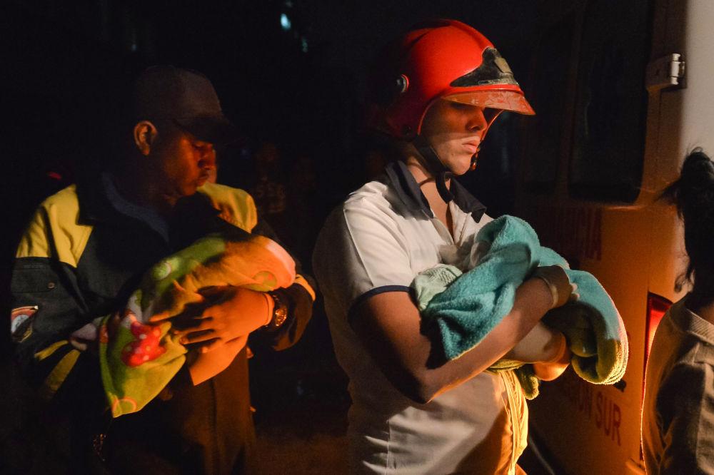 Bombeiros cubanos seguram bebês embrulhados em cobertores durante a evacuação