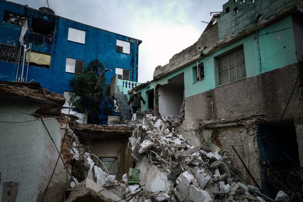 Residentes do bairro Regla caminham por escombros de prédios depois do tornado na capital de Cuba