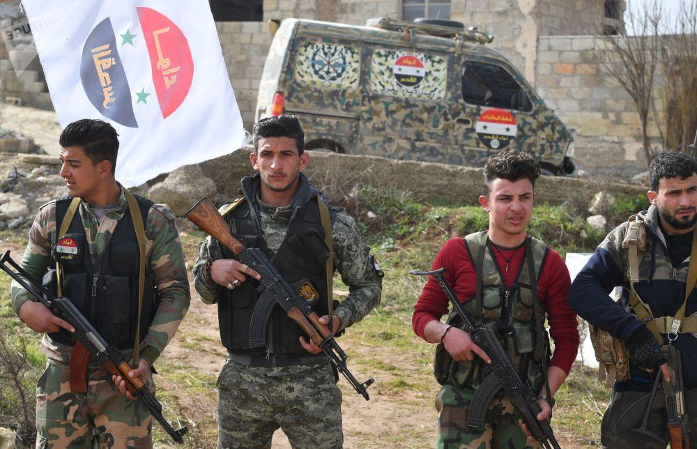 Bandeira de uma unidade da milícia libanesa ao fundo, enquanto militares russos treinam combatentes das milícias sírios, na Síria