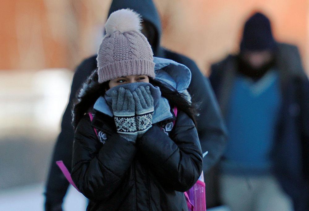Estudante reage às temperaturas baixas fechando seu rosto com mãos pelo caminho à Universidade de Minnesota, EUA, em 29 de janeiro de 2019