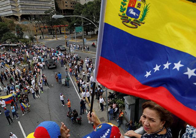 Apoiadores do autoproclamado presidente interino, Juan Guaidó, seguram bandeira enquanto participam de protesto contra o governo do presidente venezuelano Nicolás Maduro em Caracas, Venezuela, 30 de janeiro de 2019