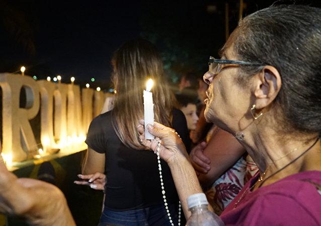 Moradora de Brumadinho é vista rezando por mortos e desaparecidos pelo rompimento da barragem de rejeitos da Vale.