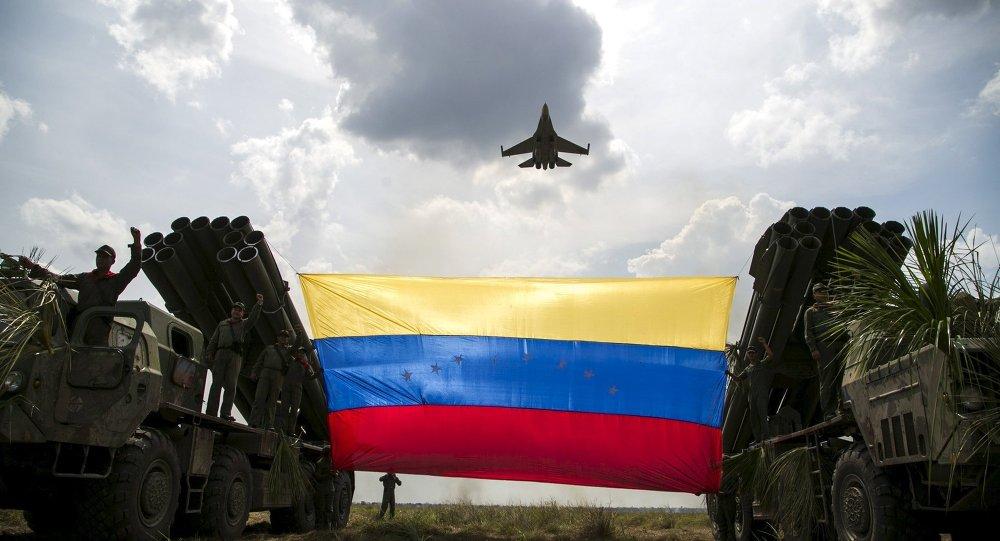 Um avião de combate Sukhoi Su-30MKV, de fabricação russa, da Força Aérea Venezuelana sobrevoa uma bandeira venezuelana