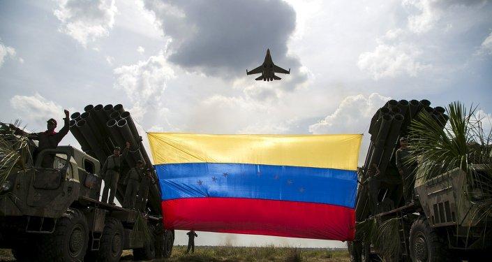 Um avião de combate Sukhoi Su-30MKV, de fabricação russa, da Força Aérea Venezuelana sobrevoa uma bandeira venezuelana.