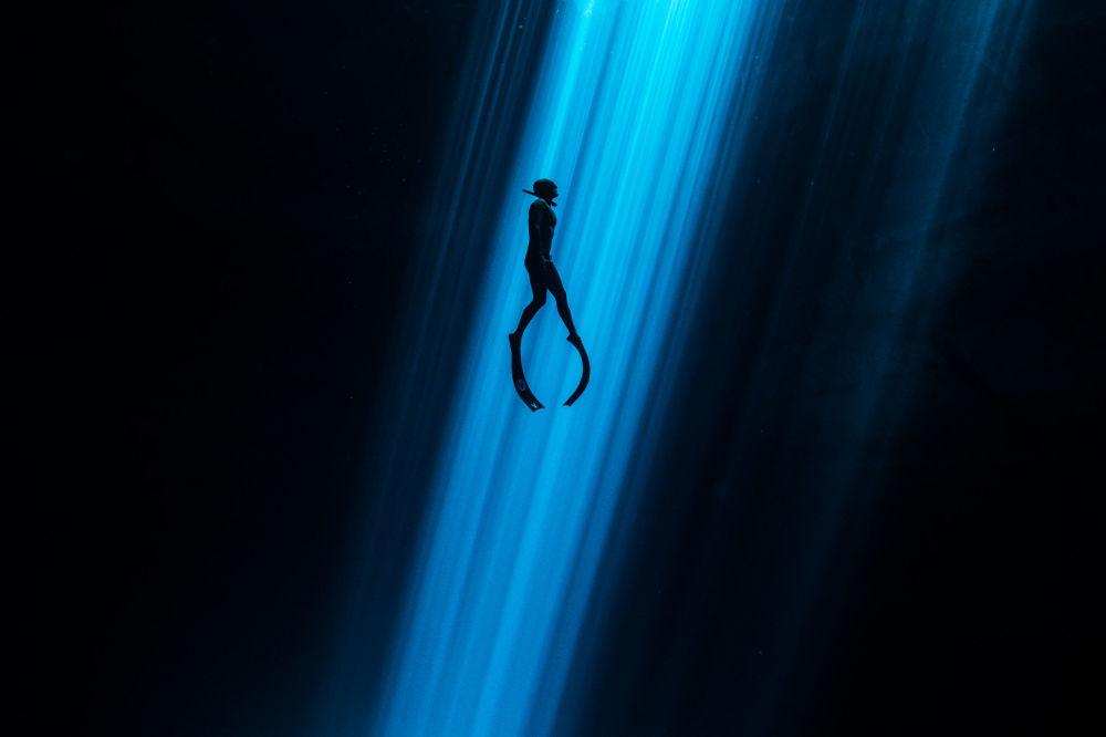 Mergulhador subindo do fundo marinho na foto de Alexandre St. Jean Feixe de luz
