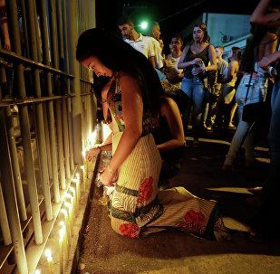 Mulher colocando velas em homenagem às vítimas em Brumadinho (MG)
