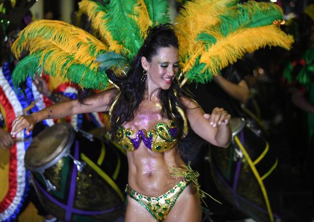 Rainha de bateria usando um belo traje verde e amarelo e dançando no desfile anual uruguaio