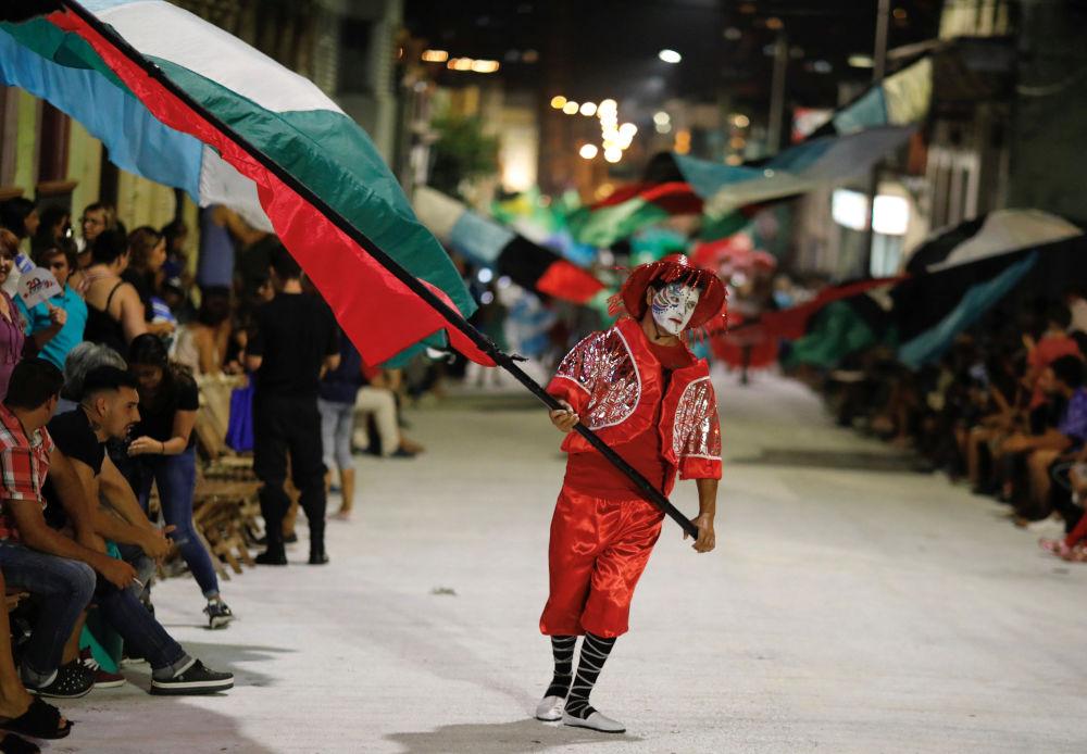 Vestindo traje vermelho, rapaz segura bandeira do grupo Comparsa na capital uruguaia, em 7 de fevereiro de 2019